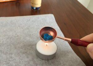 3.スプーンをろうそくで熱し、ワックスを溶かす